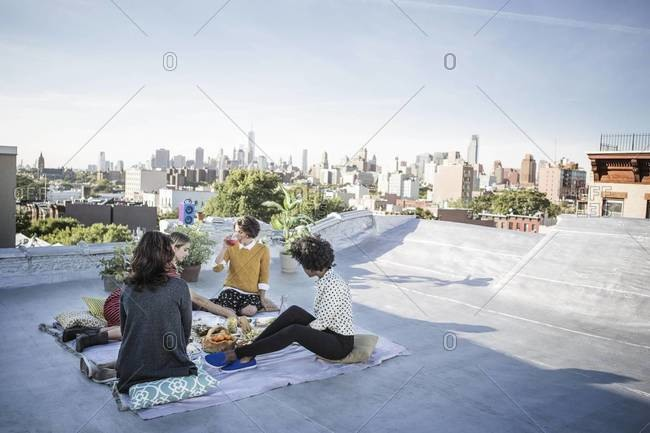 Four women having picnic on rooftop