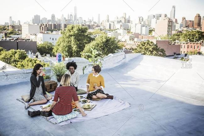 Four friends enjoying a rooftop picnic