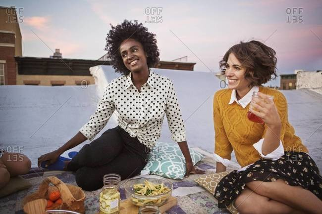 Two friends smiling during rooftop picnic