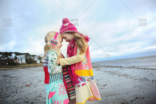 Two girls hug on a beach on a cold day