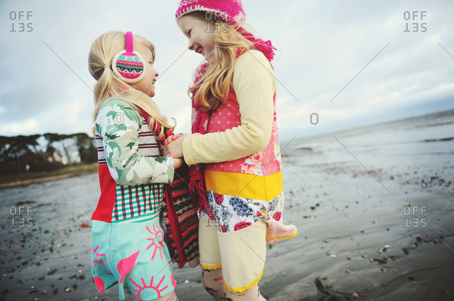 Two girls embrace on a beach on a cold day
