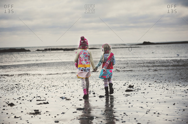 Two girls hold hands on a beach in the cold