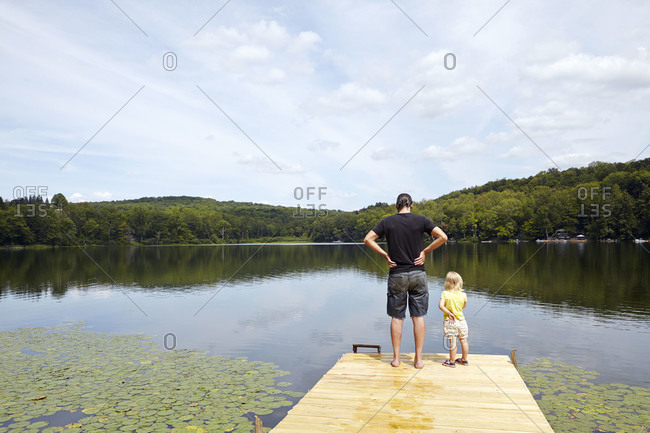 A father and daughter stand on a dock