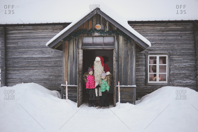 Girls and Santa Clause in doorway of house in winter
