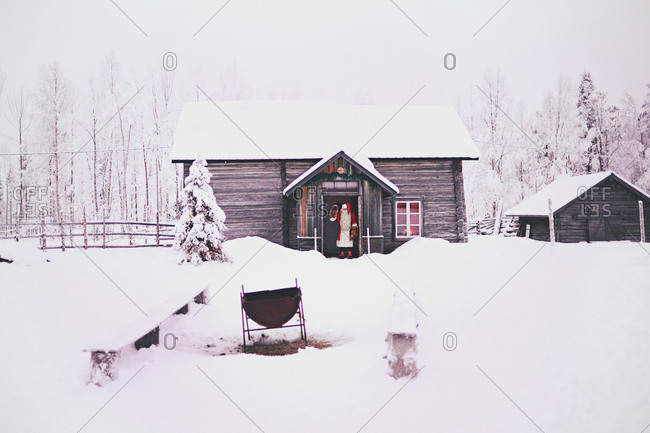 Santa Clause waving from house in winter