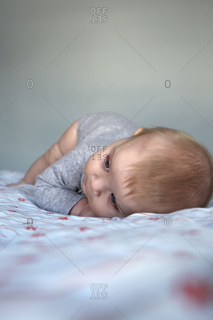 A baby lays on a bed