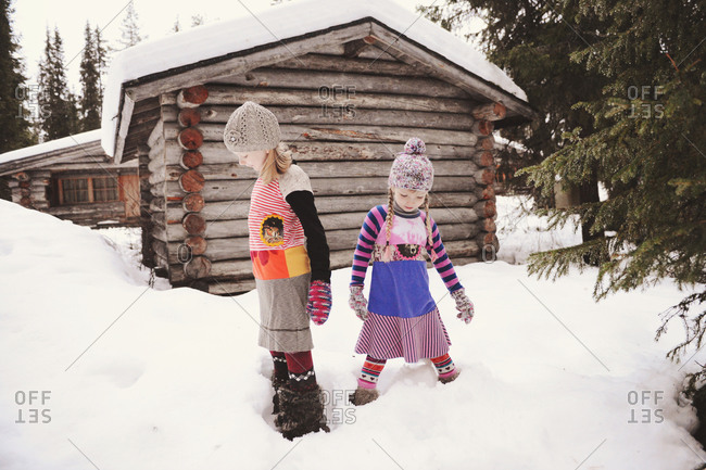 Two girls stand in deep snow near cabin