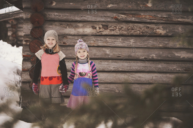 Two girls hold hands in front of cabin in snow