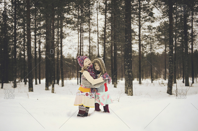 Two girls hug in snowy woods