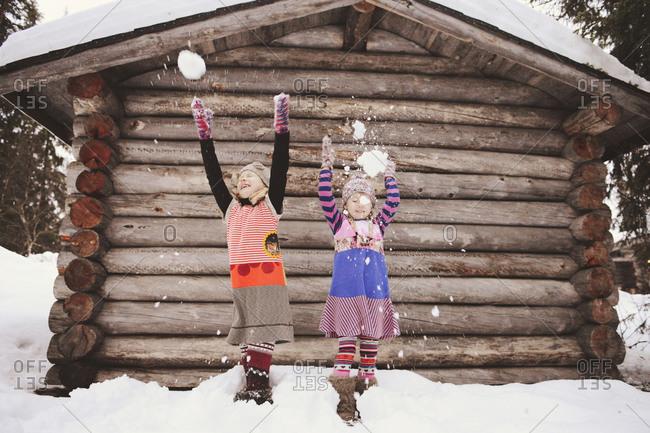 Two girls flinging snow in winter