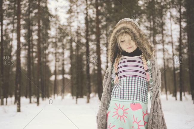 Portrait of girl in fur lined hoodie outside in snow