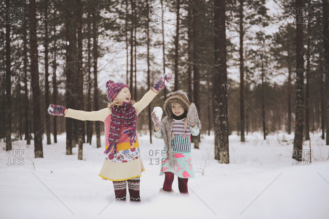 Two girls play with snow in woods