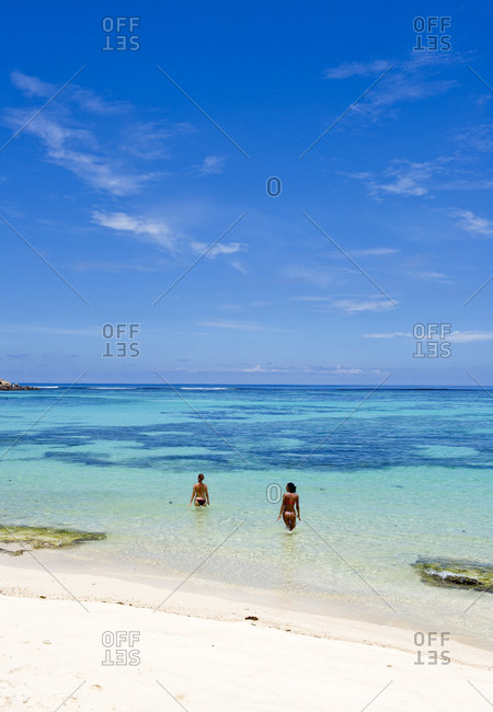 Two women wading into ocean at Seychelles beach