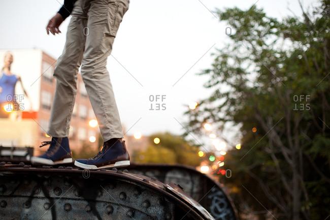Boy standing on low metal bridge
