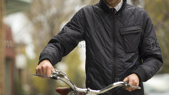 Mid-section of man walking his bicycle