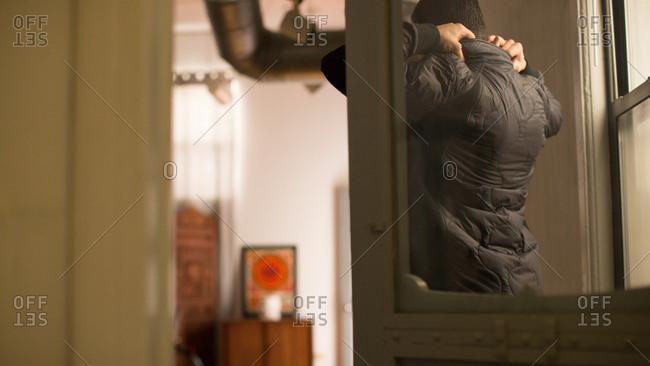Man adjusting jacket collar in apartment