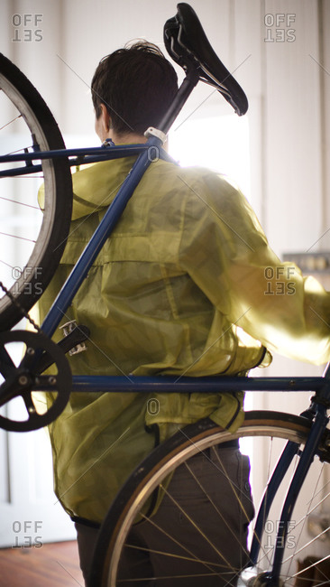 Man in yellow jacket lifting bicycle