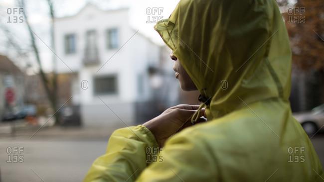Mad adjusting hood of rain coat in street