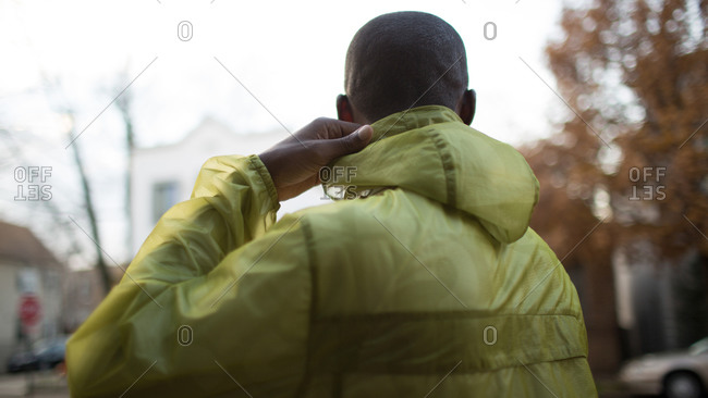 Man adjusting rain coat hood outside