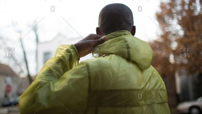 Man adjusting rain coat hood outside