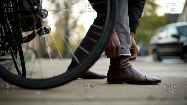 Man by bike tire adjusting pants hem