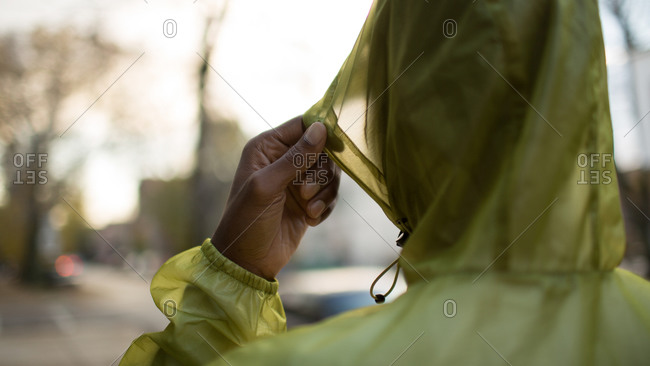Man pulling up rain coat hood