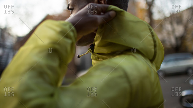 Close up of man adjusting the hold of his rain coat