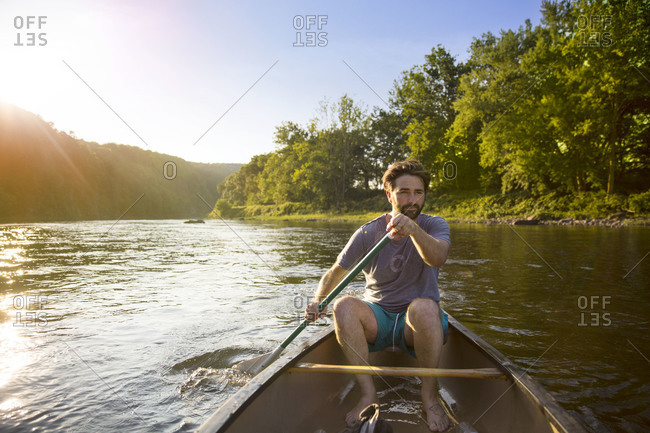 Man rowing down river in sunlight