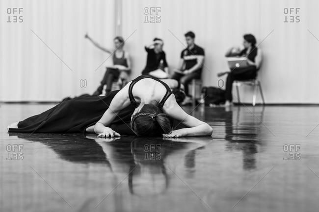 A dancer bows to the ground during rehearsal