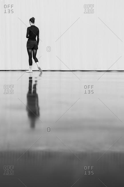 A dancer walks to the far end of a dance studio