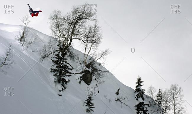 Snowboarder jumping off snowy piste, Arlberg, Austria