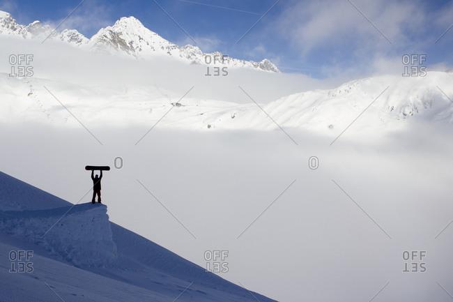 Snowboarder raising his board in triumph on a ski-jump, Arlberg, Austria