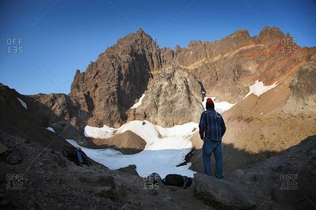 Hiker looking up at rocky peak, central Oregon
