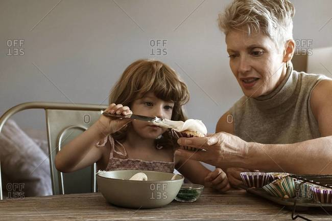 Young girl spreading frosting on cupcakes with her grandmother