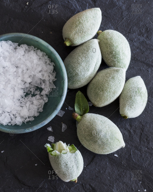 Green almonds and salt in bowl