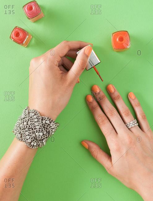 Woman painting her fingernails - Offset