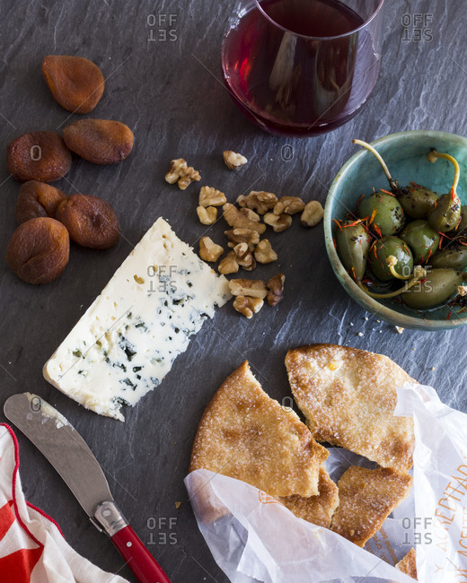 Bread and cheese served with nuts and dried apricots