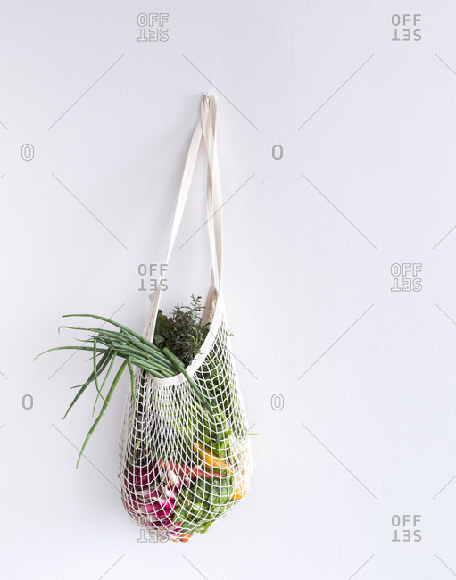 Fresh vegetables in a bag hanging on a wall