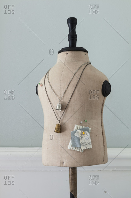 Dressmaking mannequin with thimble necklaces