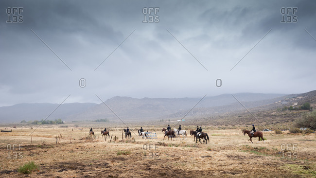 Horse riders in traditional black coats riding in the Nevada desert under ominous rain clouds, USA