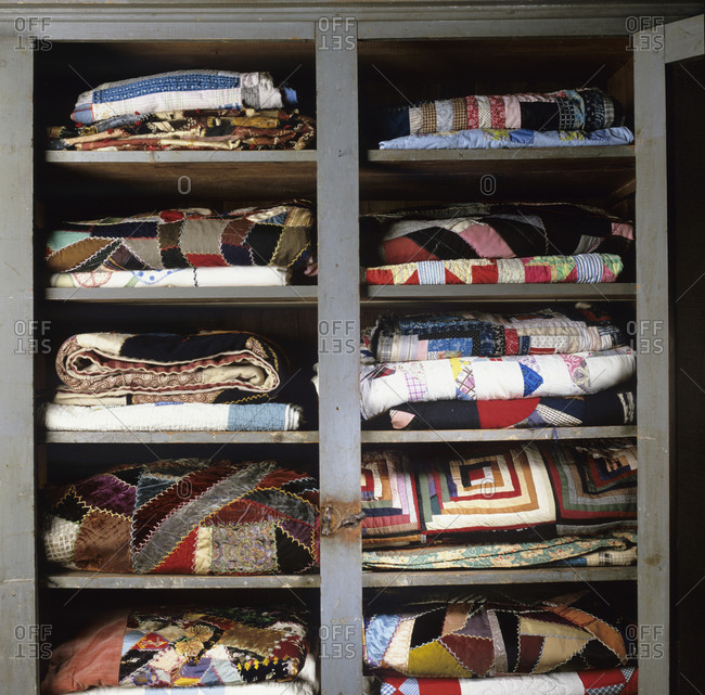 A display of folded antique quilts