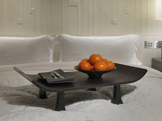 Breakfast tray with oranges on bed in modern hotel room