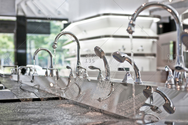 Faucets with running water on in kitchen and bath showroom