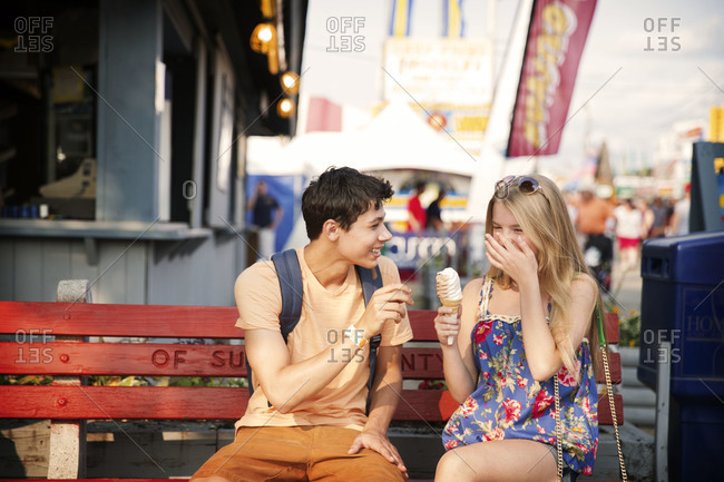 Teenage couple laughing and eating ice cream on a bench at a county fair