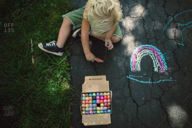 Boy drawing a rainbow in chalk