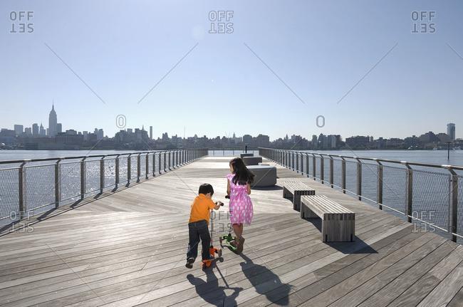 Two children on pier overlooking Manhattan