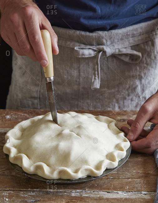 Man cutting vents into pie crust