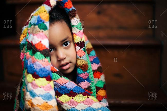 Little girl wrapped herself in a colorful crochet blanket