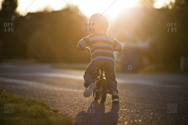 Little boy riding bike on street in the evening