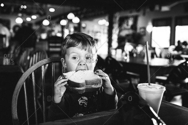 Boy biting into sandwich at a restaurant